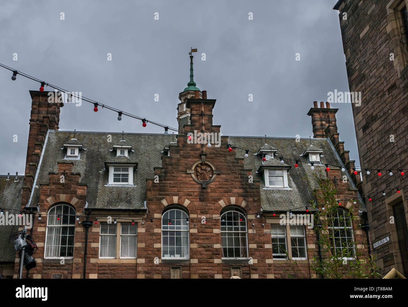 Edinburgh, Scotland, UK, August 7th 2017.  Assembly Roxy fairy lights outside in street with view of roof and windows of a Victorian primary school now converted into flats - Stock Image