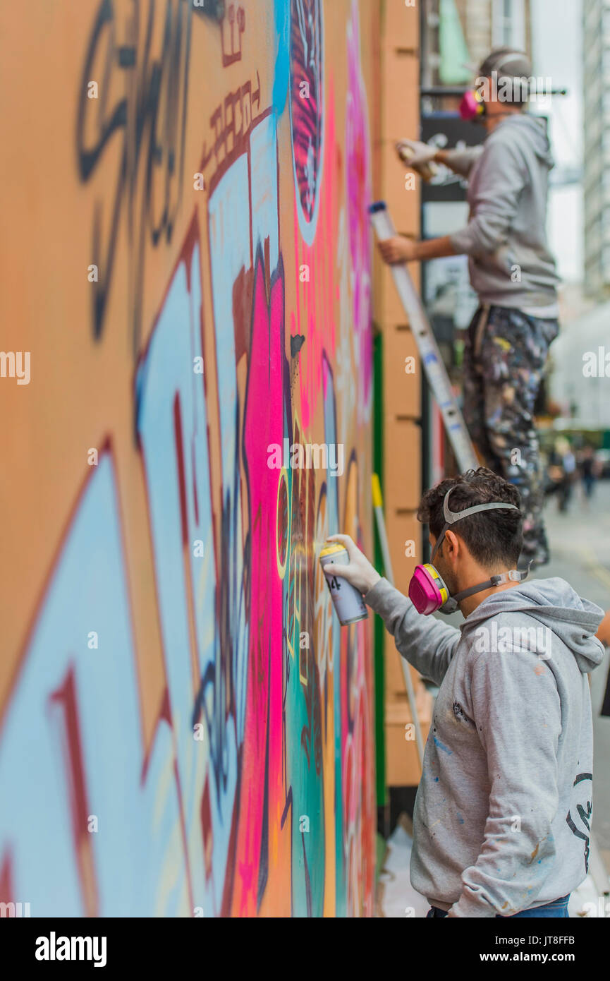 London, UK. 8th Aug, 2017. Their work Apollo takes shape in Berwick Street. PichiAvo: In Gods We Trust – a new commission and exhibition at Unit London, Wardour Street, by Spanish artists PichiAvo. Both the exterior facade and interior walls of Unit London's downstairs gallery are colour covered from head-to-foot by PichiAvo's unique blend of graffiti and fine art styles. Credit: Guy Bell/Alamy Live News - Stock Image