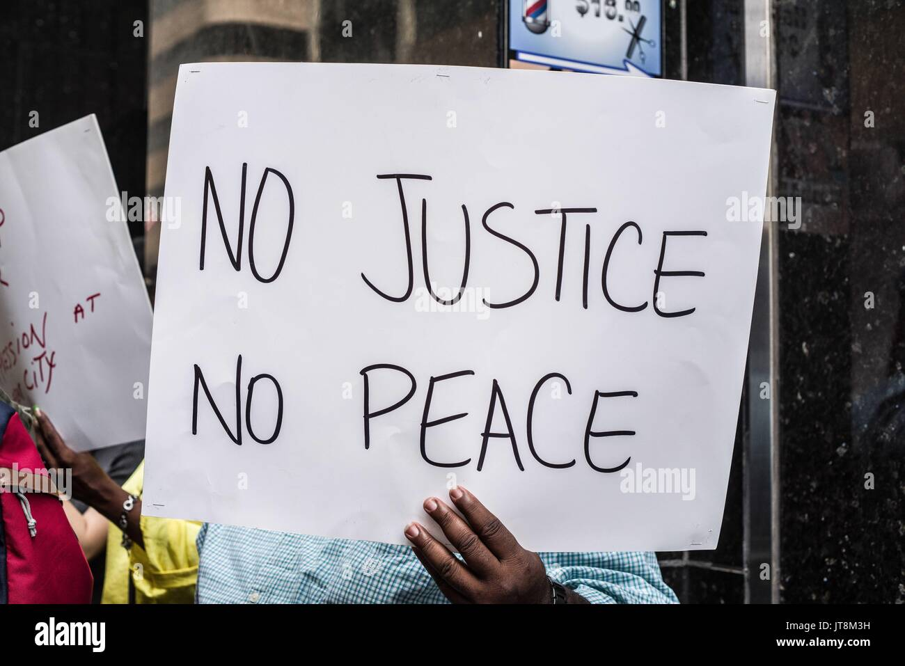 New York City, New York, USA. 8th Aug, 2017. A man holds a ''no justice no peace'' sign. Headed by Dr. Rev Phil Craig of Al Sharpton's National Action Network, a group of voters from Lefrak City in Queens allege irregularities and attempts to change the demographics of the votes in their district via a closure of their local voting office. The local office has been open for more than three decades, according to demonstrators. This is the latest in a series of rallies for 'election integrity'' that have popped up around the city from unconnected groups. The prote - Stock Image