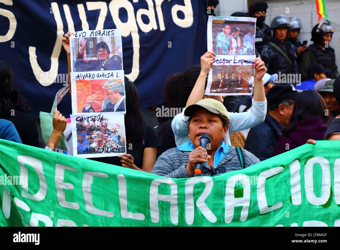 La Paz, Bolivia, 8th August 2017. TIPNIS Subcentral indigenous leader Marqueza Teco speaks at a meeting to show opposition to government plans to annul Law 180, which is being debated today in the senate. Behind her protesters hold blood covered photos of Bolivian president Evo Morales, vice president Alvaro Garcia Linera and other public figures. Credit: James Brunker / Alamy Live News - Stock Image