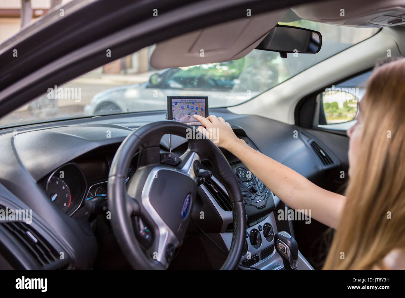 Young Woman In A Car Using A Gps To Get Driving Directions To Her