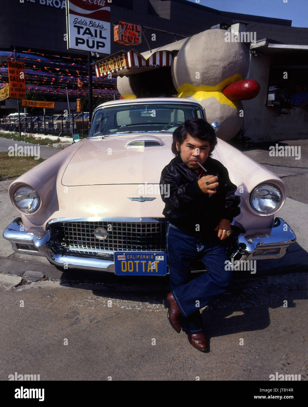 Portrait of actor Herve Villechaize with his classic T-Bird with vanity plate reading Tattoo backwards at the Tail o The Pup hot dog stand in West Hollywood circa 1984 - Stock Image