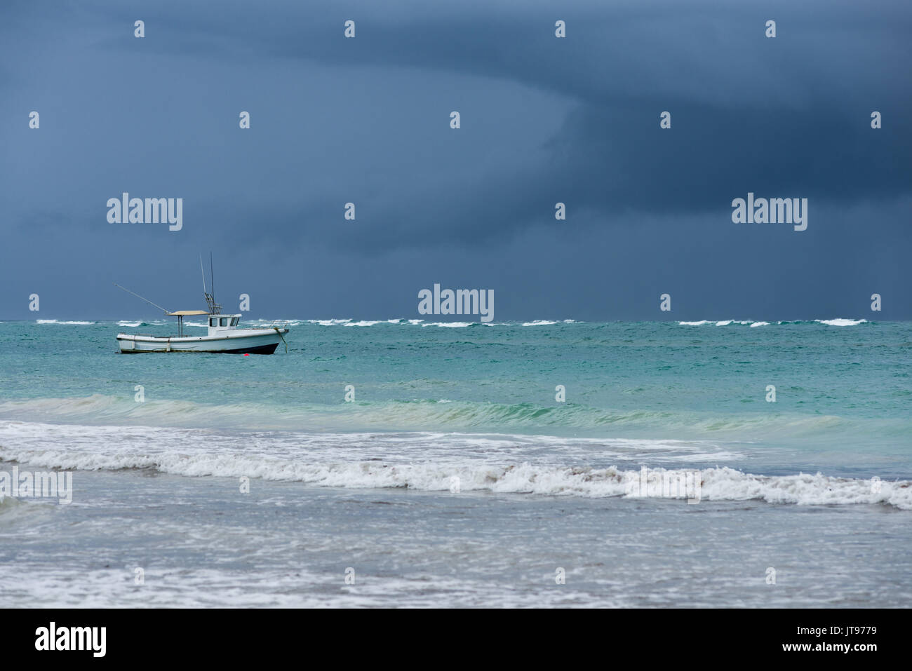 Fishing boat anchored by shore with rain cloud in background, Diani, Kenya - Stock Image