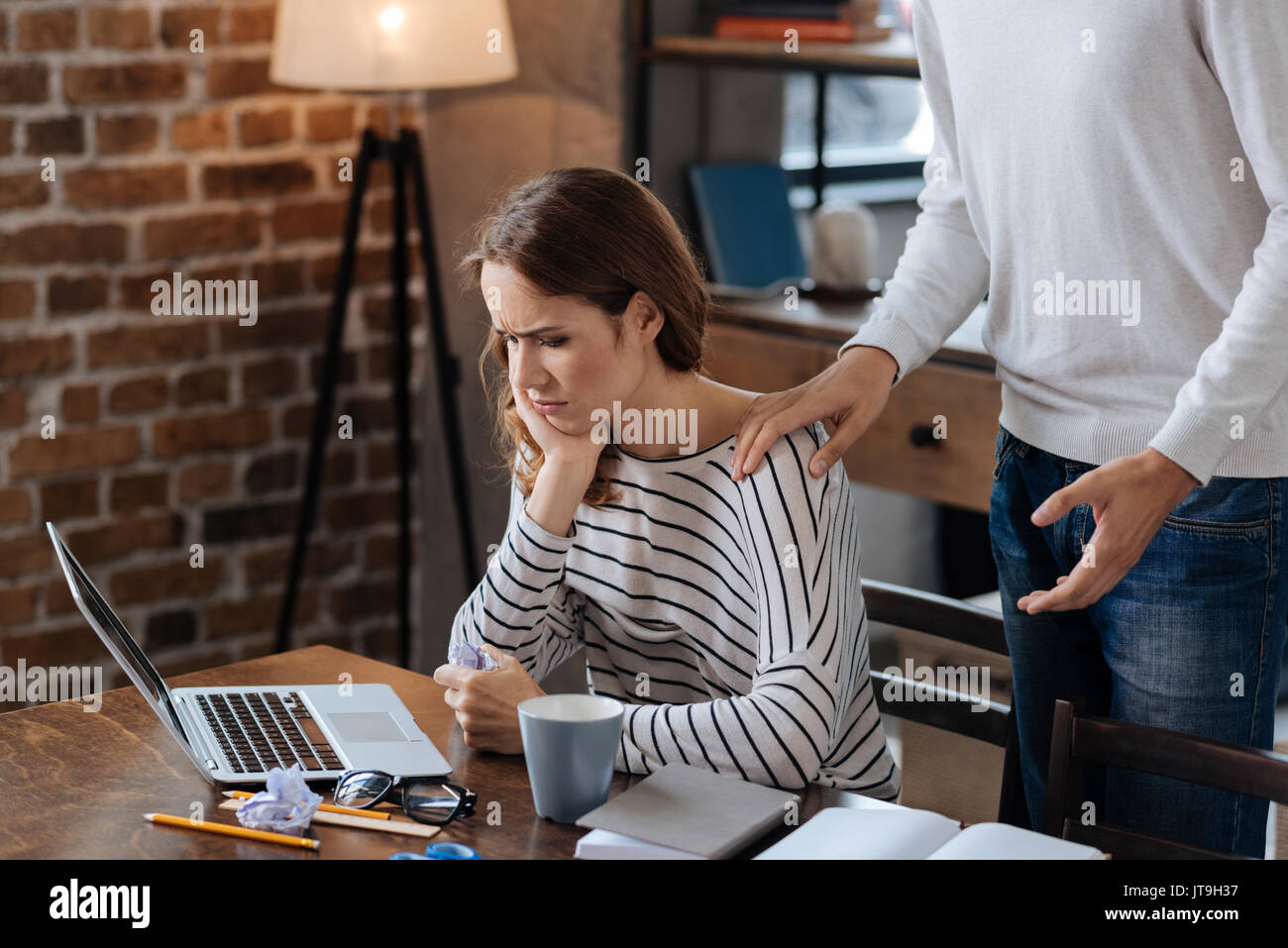 Cheerless thoughtful woman looking at the laptop screen - Stock Image