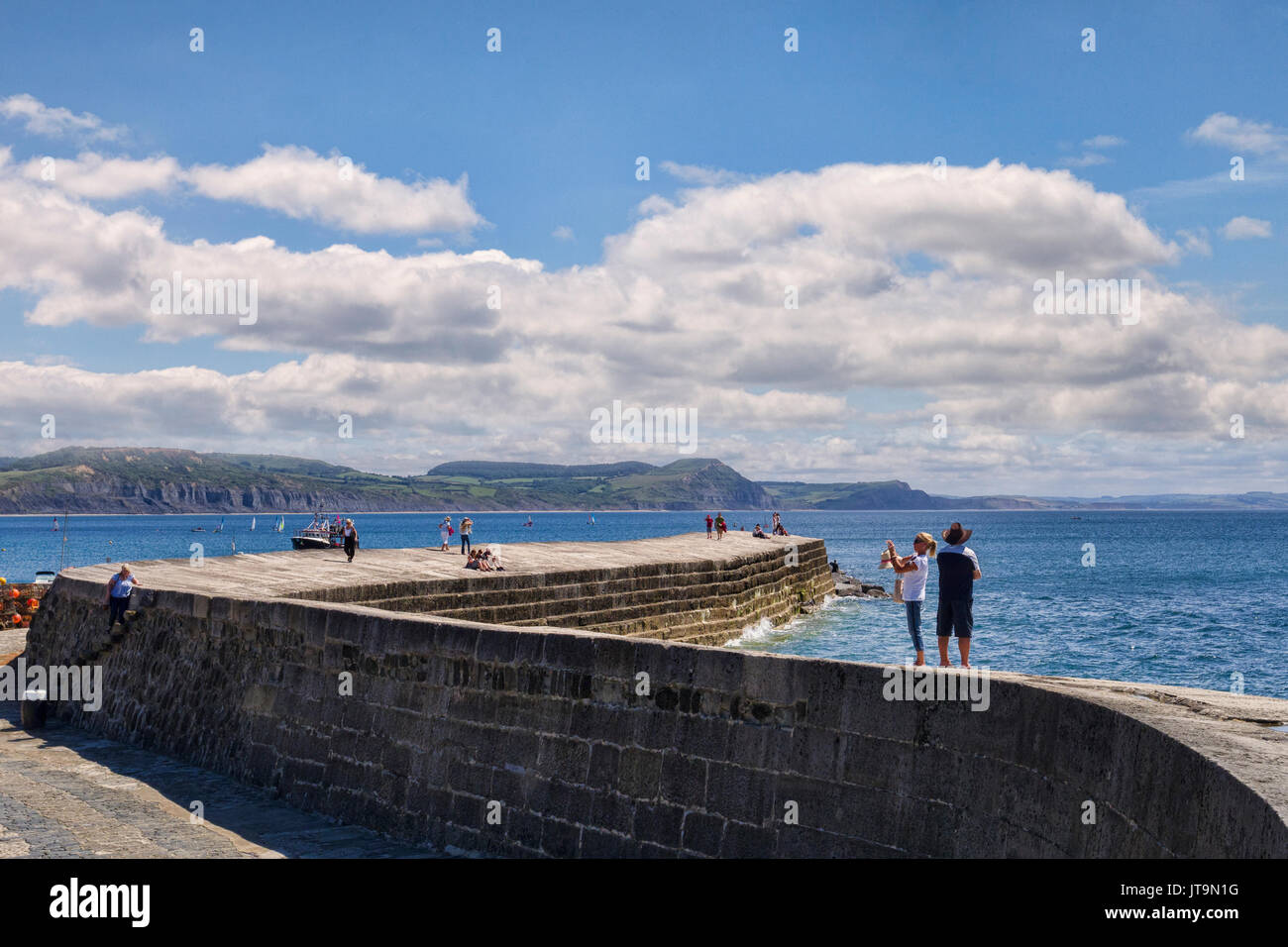 1 July 2017: Lyme Regis, Dorset, England, UK - Visitors strolling on The Cobb on a beautiful sunny summer day. - Stock Image