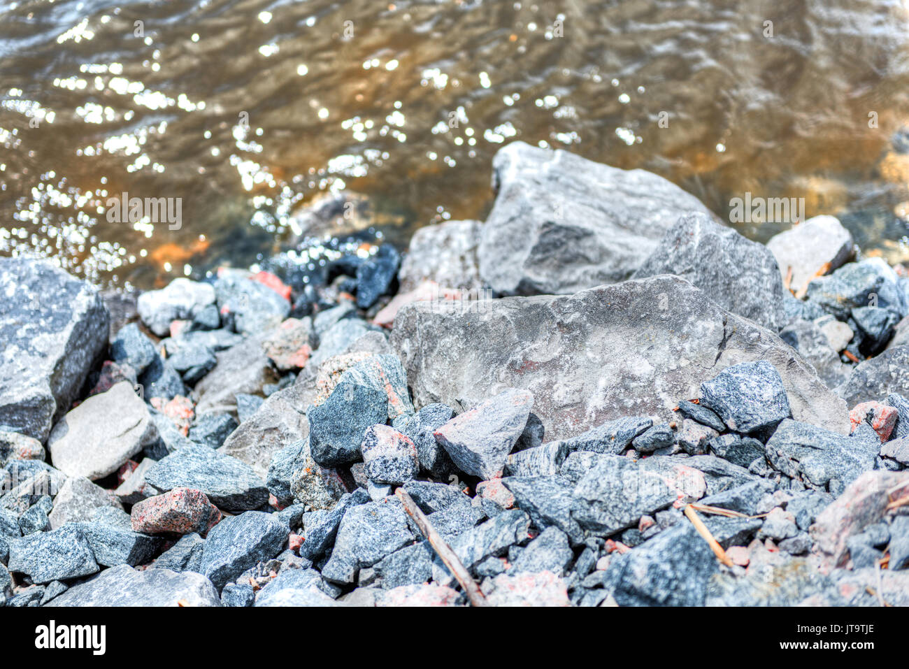 Colorful rocks on Saint Laurent or Lawrence river in Quebec, Canada during summer with brown water Stock Photo