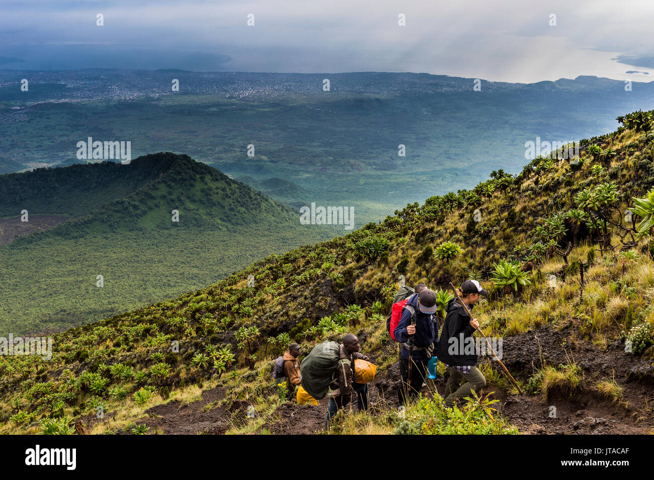 Trekkers on the steep slopes of Mount Nyiragongo, Virunga National Park, Democratic Republic of the Congo, Africa - Stock Image