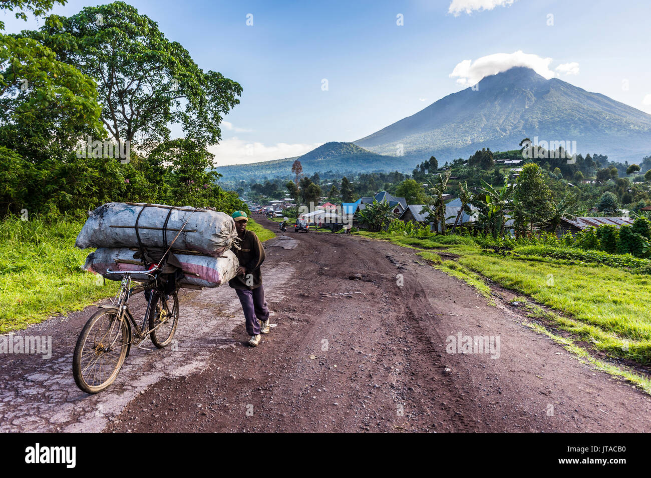 Man carrying a lot of bags on a bicycle, Virunga National Park, Democratic Republic of the Congo, Africa - Stock Image