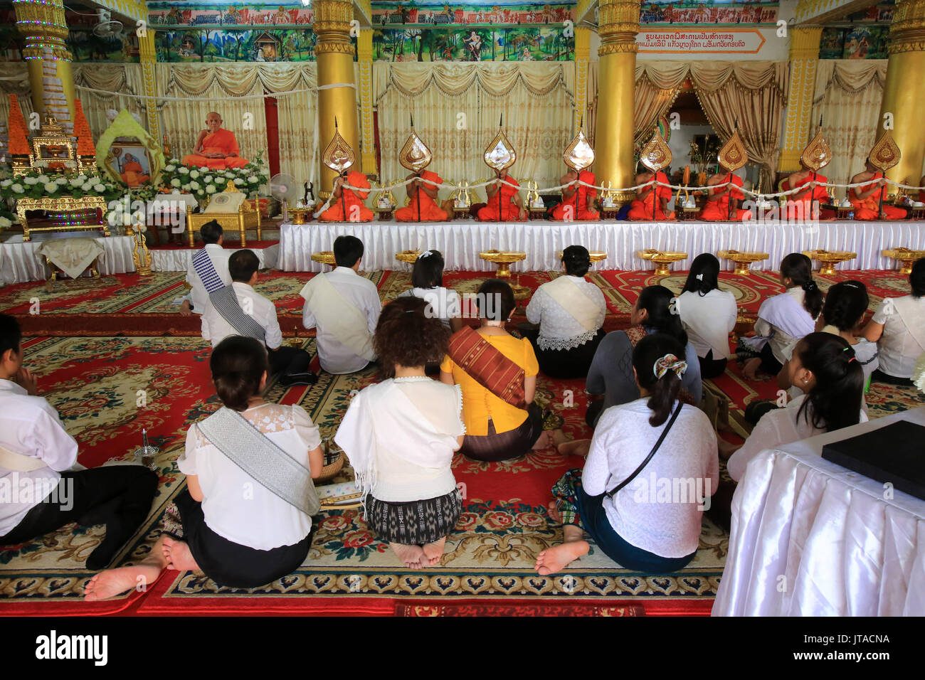 Buddhist monks praying at Remembrance of the Deceased, Wat Ong Teu Mahawihan (Temple of the Heavy Buddha), Vientiane, Stock Photo