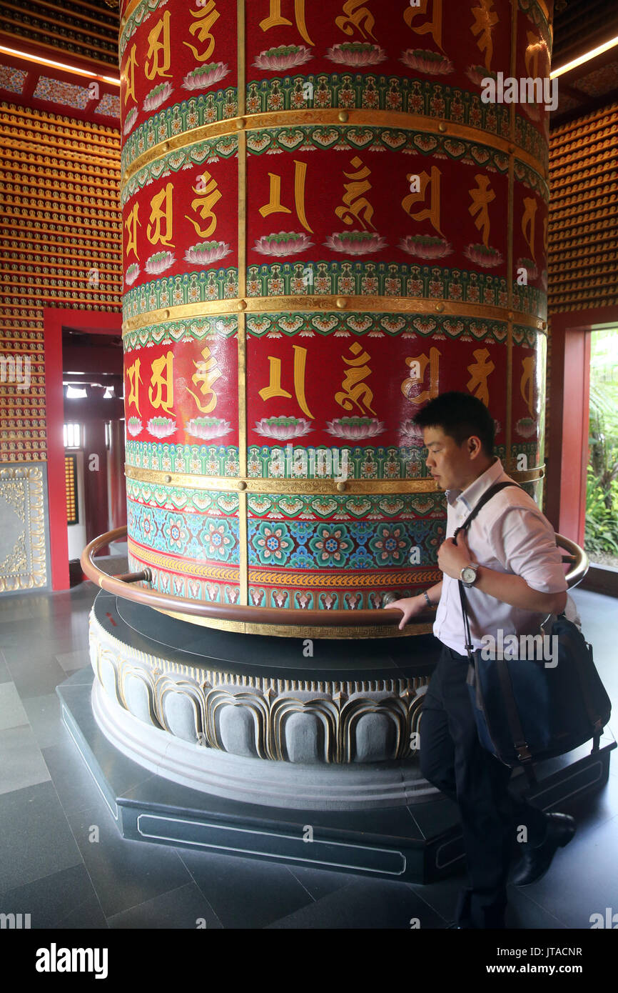 Worshipper and Viarocana Buddhist prayer wheel, Buddha Tooth Relic Temple in Chinatown, Singapore, Southeast Asia, Asia - Stock Image