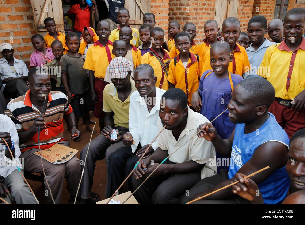 Ugandan villagers drinking home-brewed beer and schoolchildren, Bweyale, Uganda, Africa - Stock Image