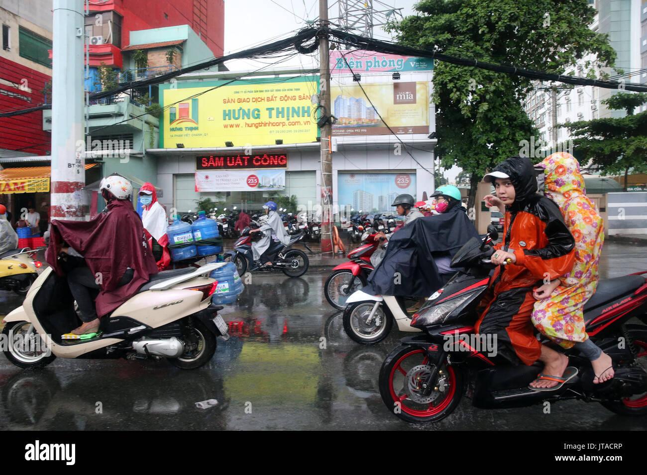 Motor scooters on Saigon Street in heavy monsoon rain, Ho Chi Minh City, Vietnam, Indochina, Southeast Asia, Asia - Stock Image