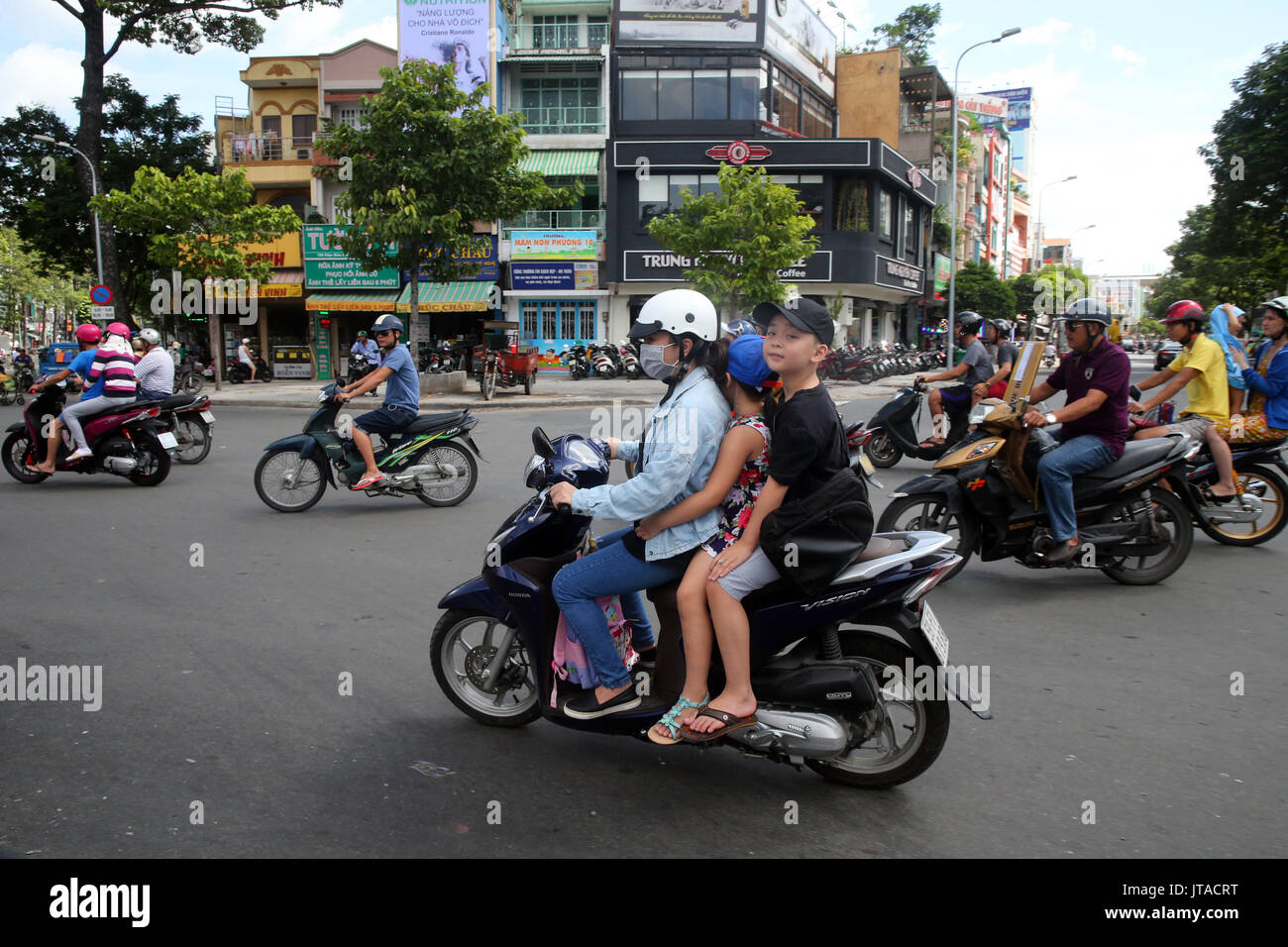 Mother and children on motor scooter on Saigon Street, Ho Chi Minh City, Vietnam, Indochina, Southeast Asia, Asia - Stock Image