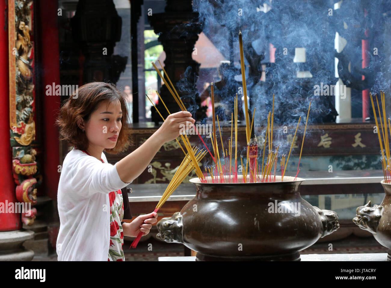 Buddhist worshipper placing incense sticks on joss stick pot, Taoist temple, Phuoc An Hoi Quan Pagoda, Ho Chi Minh City, Vietnam - Stock Image