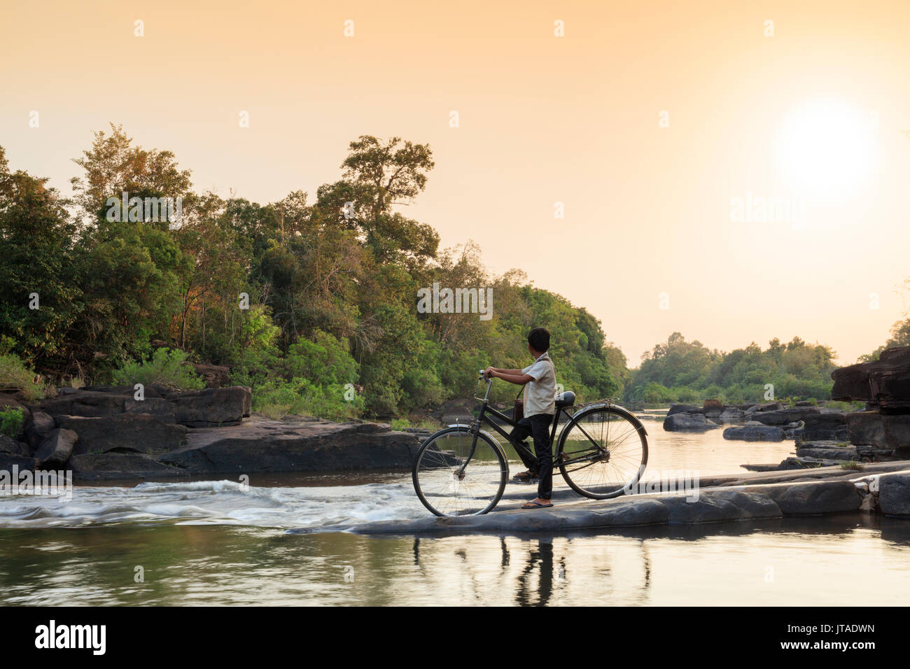 School boy on a bicycle crossing a river on his way to school, Chi Phat, Koh Kong, Cambodia, Indochina, Southeast Asia, Asia - Stock Image
