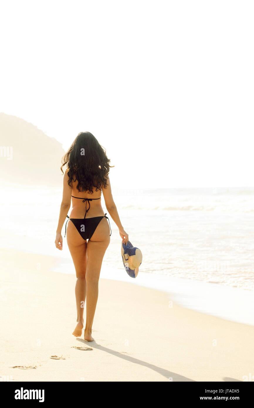 Young Brazilian (Latin American) (Latina) woman in golden dawn light on the beach in a bikini, Rio de Janeiro, Brazil - Stock Image