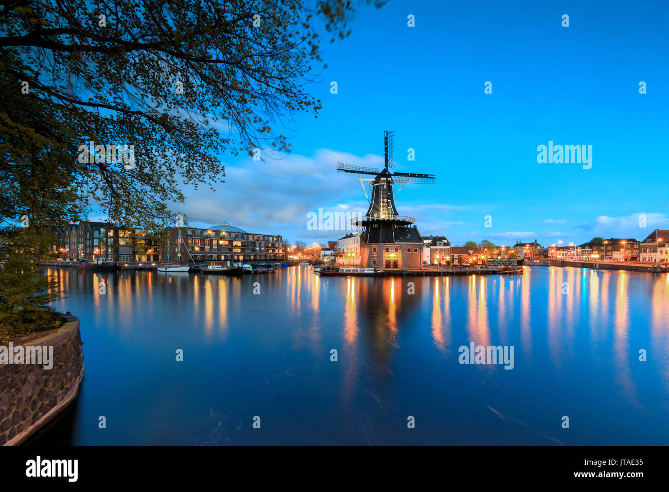 Dusk lights on the Windmill De Adriaan reflected in the River Spaarne, Haarlem, North Holland, The Netherlands, Europe - Stock Image