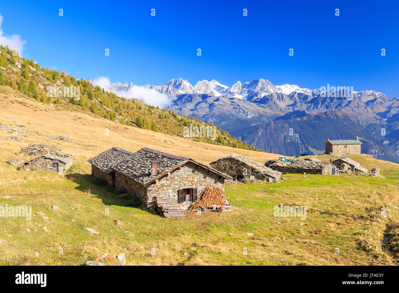Alpine huts framed by snowy peaks of Bernina Group, Arcoglio Alp, Val Torreggio, Malenco Valley, Valtellina, Lombardy, Stock Photo