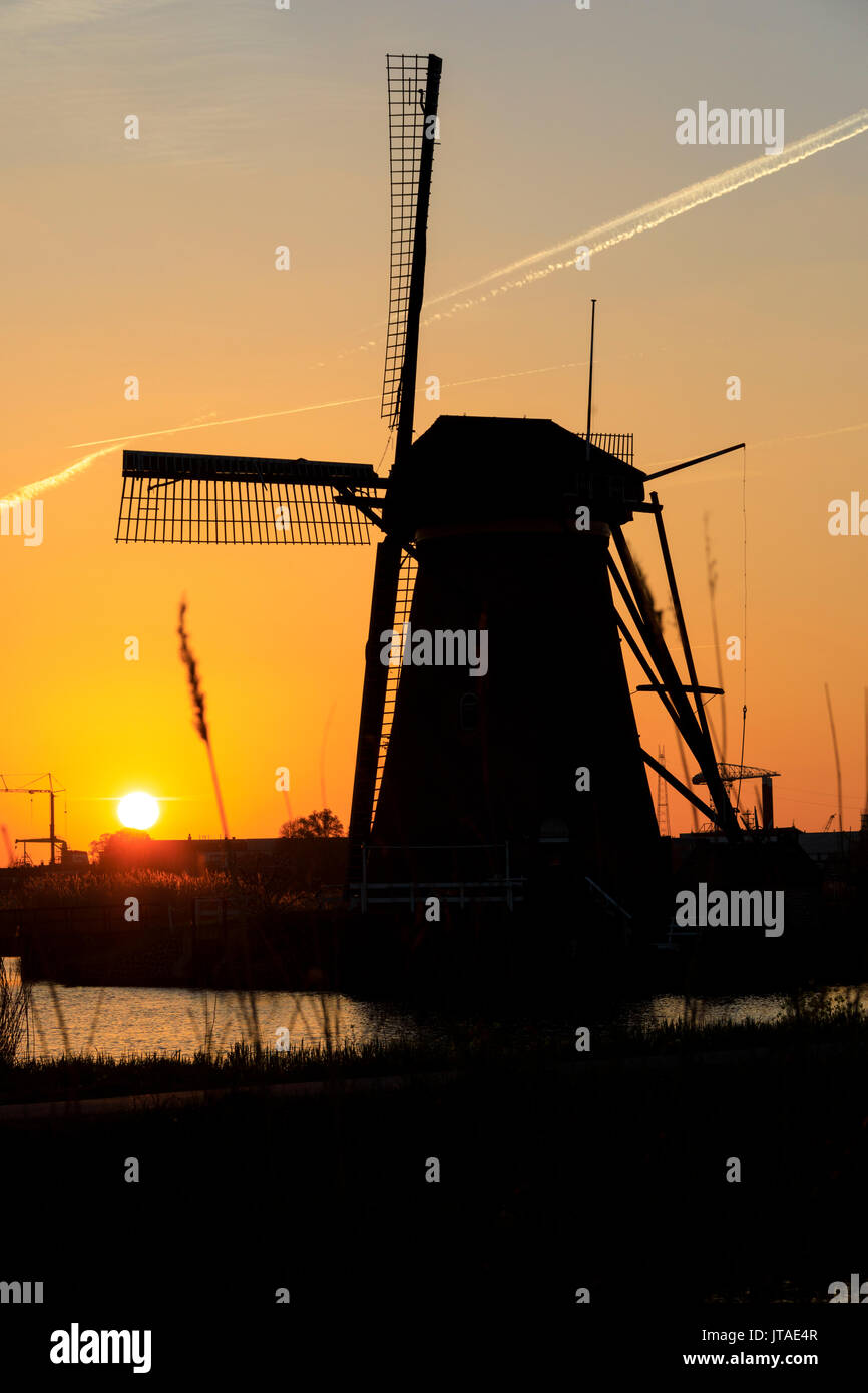 Silhouette of typical windmill framed by the fiery sky at sunset, Kinderdijk, UNESCO, Molenwaard, South Holland, Stock Photo