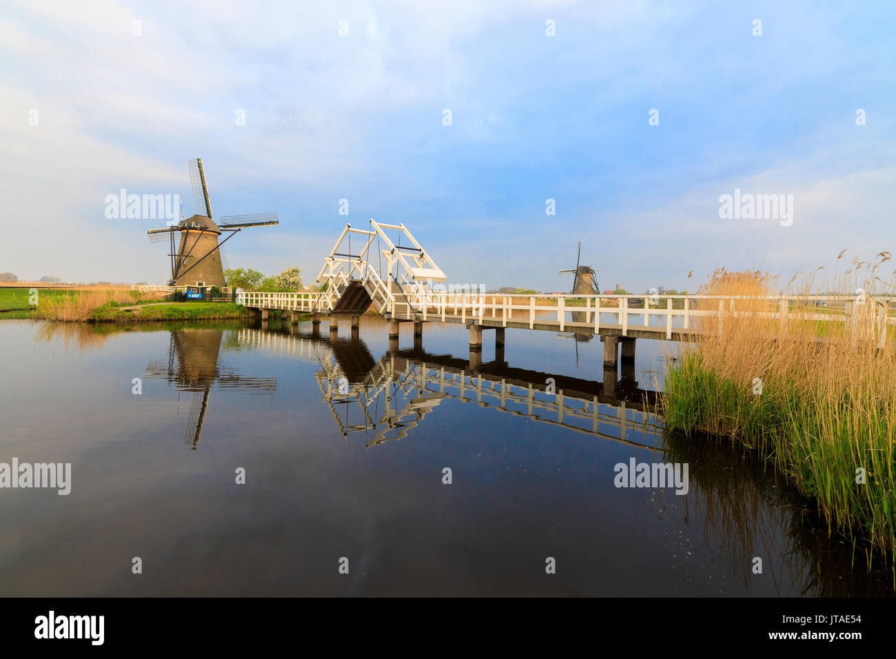 Traditional windmills and bridge on the canal framed by sunrise, Kinderdijk, UNESCO, Molenwaard, South Holland, Stock Photo