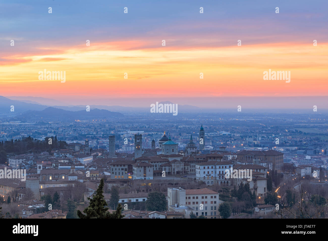 View of the medieval old town called Citta Alta on hilltop framed by the fiery orange sky at dawn, Bergamo, Lombardy, Italy - Stock Image