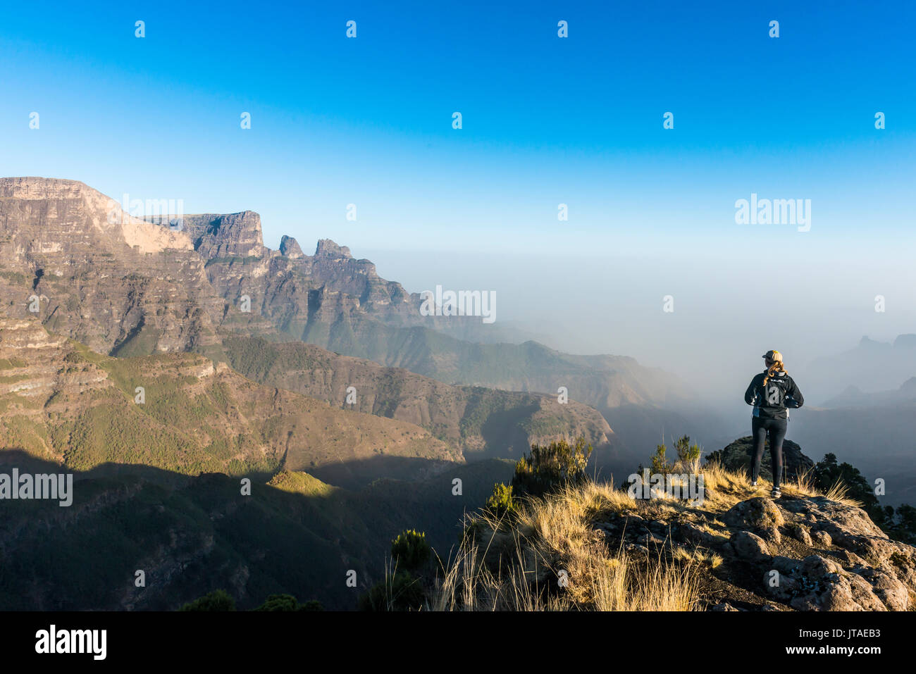 Woman enjoying the early morning sun on the cliffs, Simien Mountains National Park, UNESCO, Debarq, Ethiopia, Africa - Stock Image