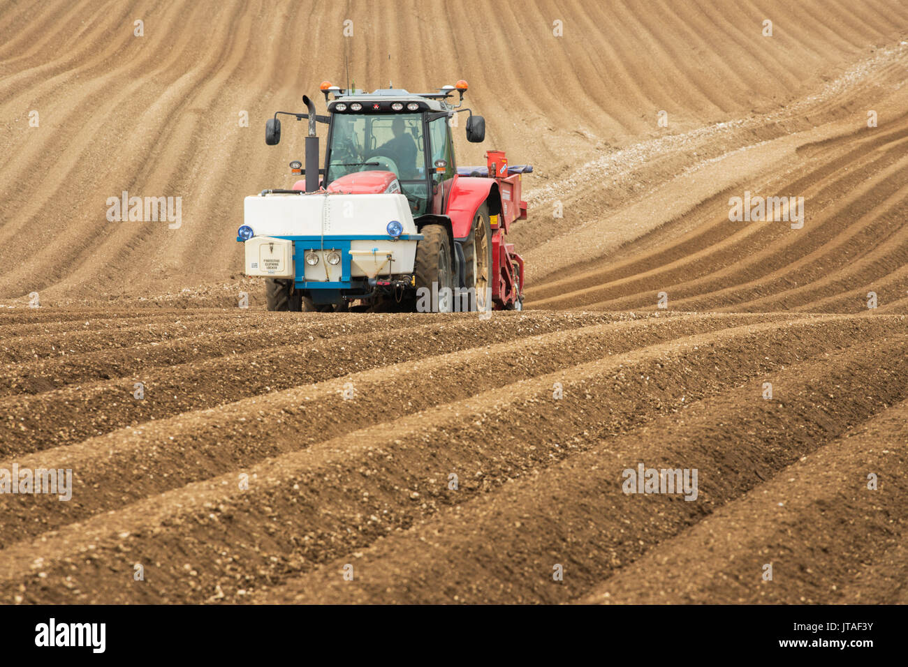 Farmer ploughing and cultivating field for crops near Fridaythorpe, Yorkshire Wolds, East Yorkshire, England, United Kingdom - Stock Image