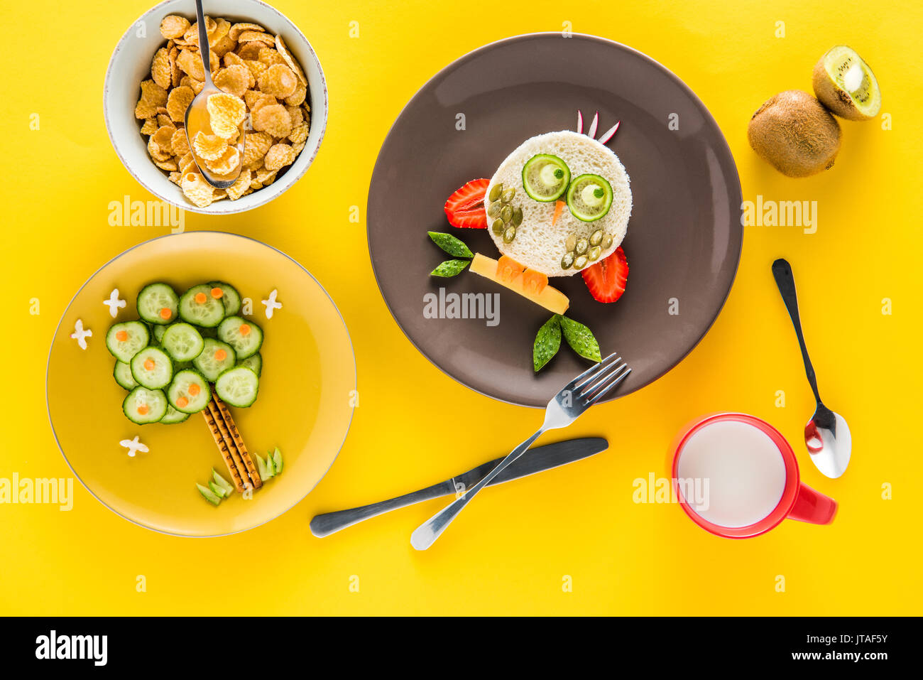 Funny colorful breakfast for child in shape of owl and tree with cornflakes, kiwi and milk isolated on yellow Stock Photo