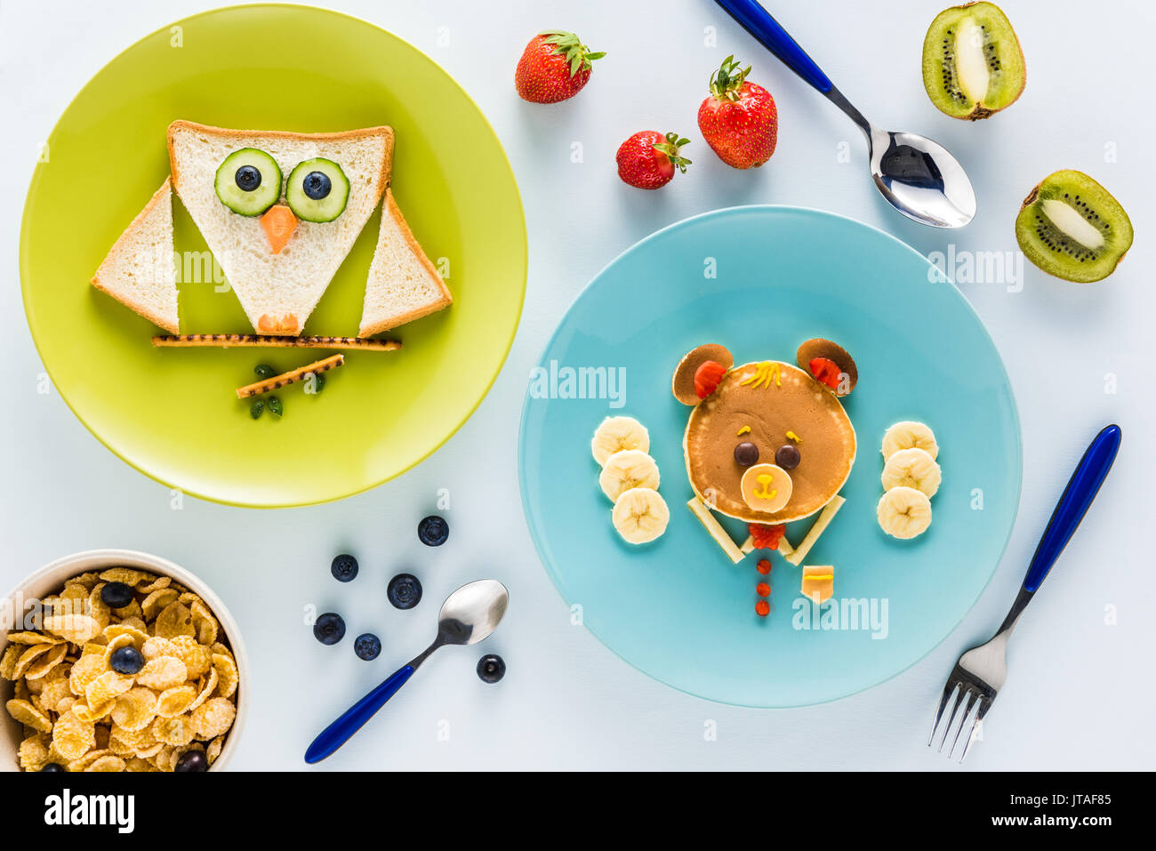 flat lay with creatively styled children's breakfast with berries and kiwi - Stock Image