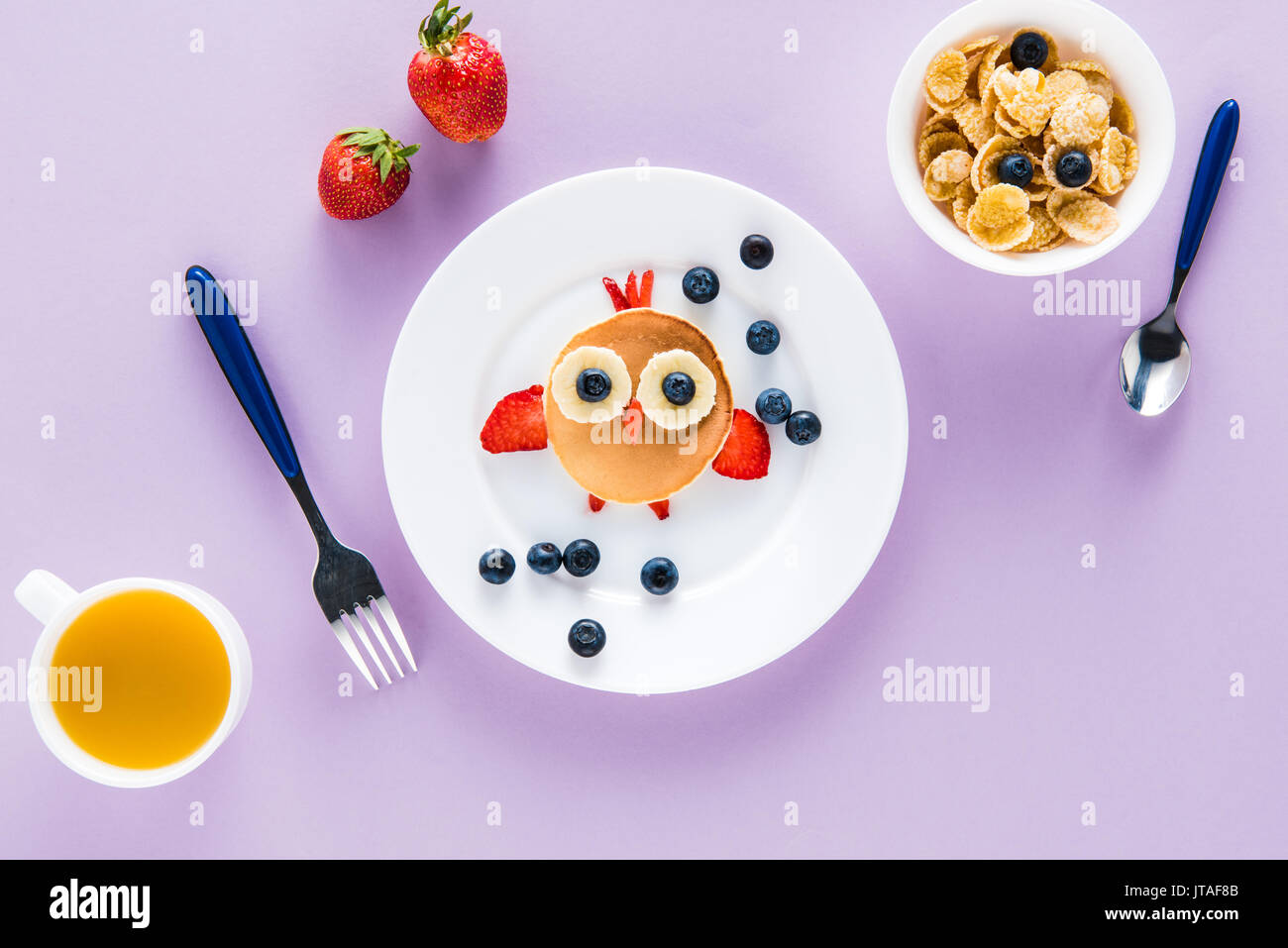 flat lay with creatively styled children's breakfast on colorful tabletop - Stock Image