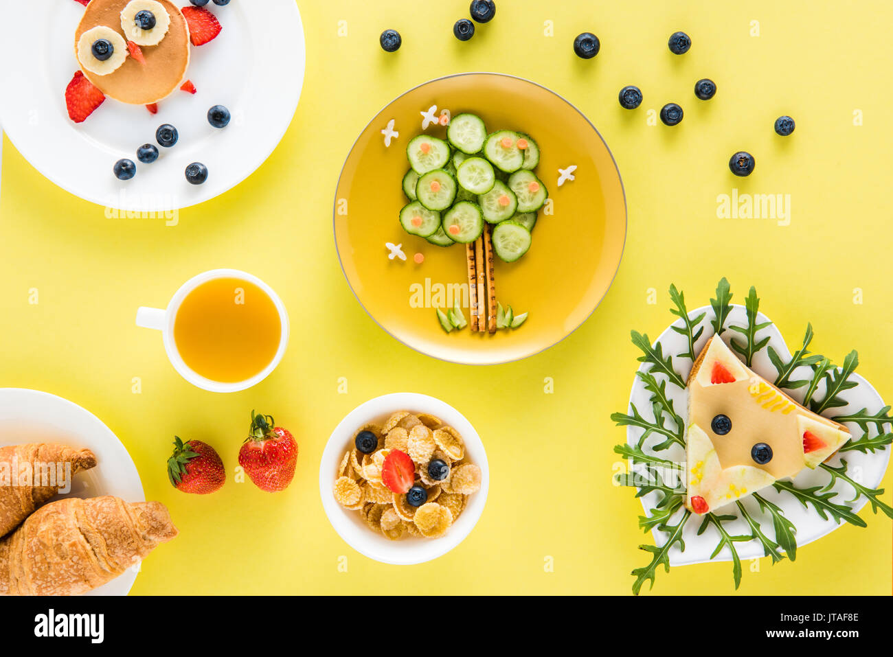 top view of creatively styled children's breakfast with croissants and juice - Stock Image