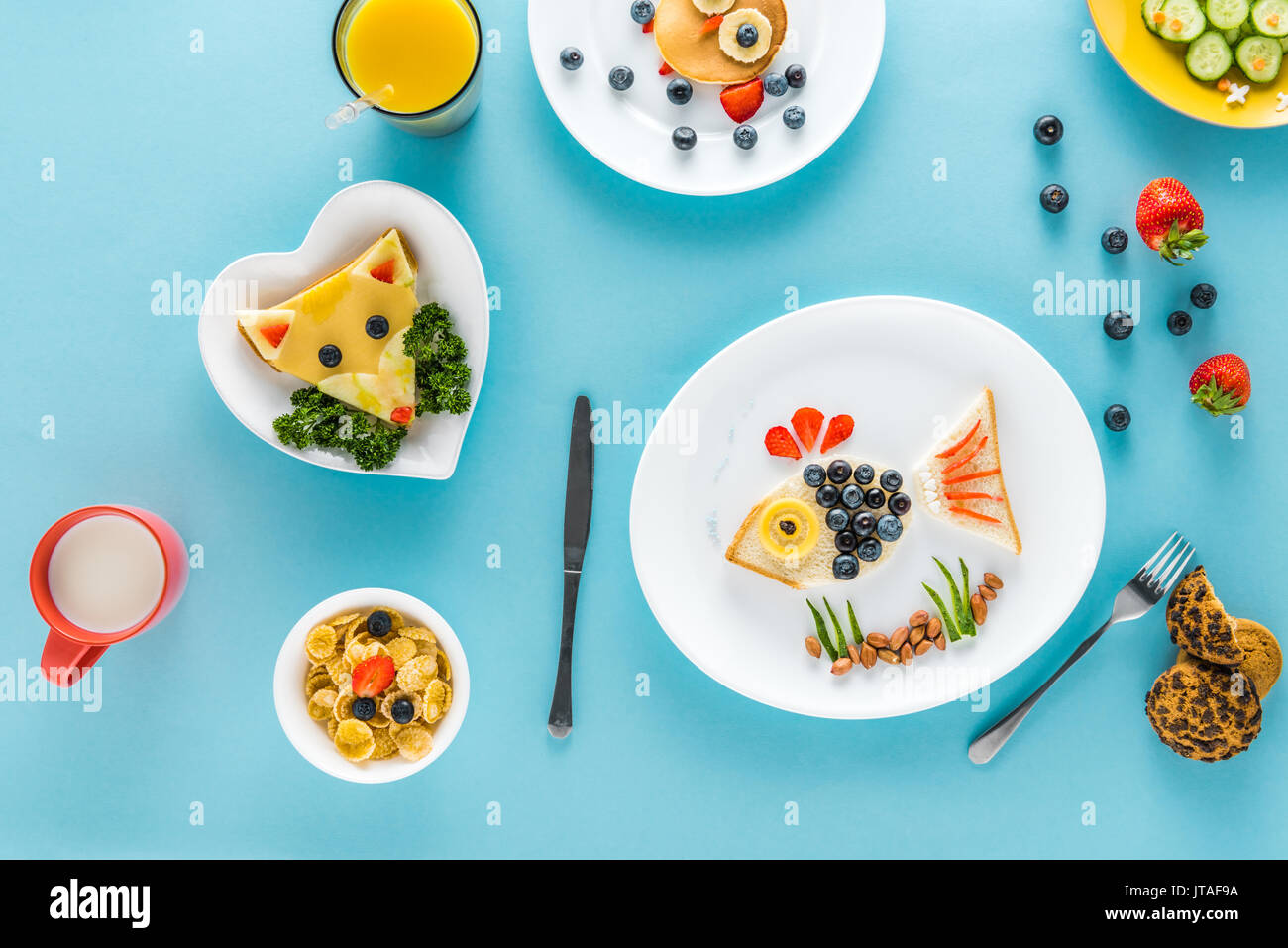 flat lay with creatively styled children's breakfast with juice on colorful tabletop - Stock Image