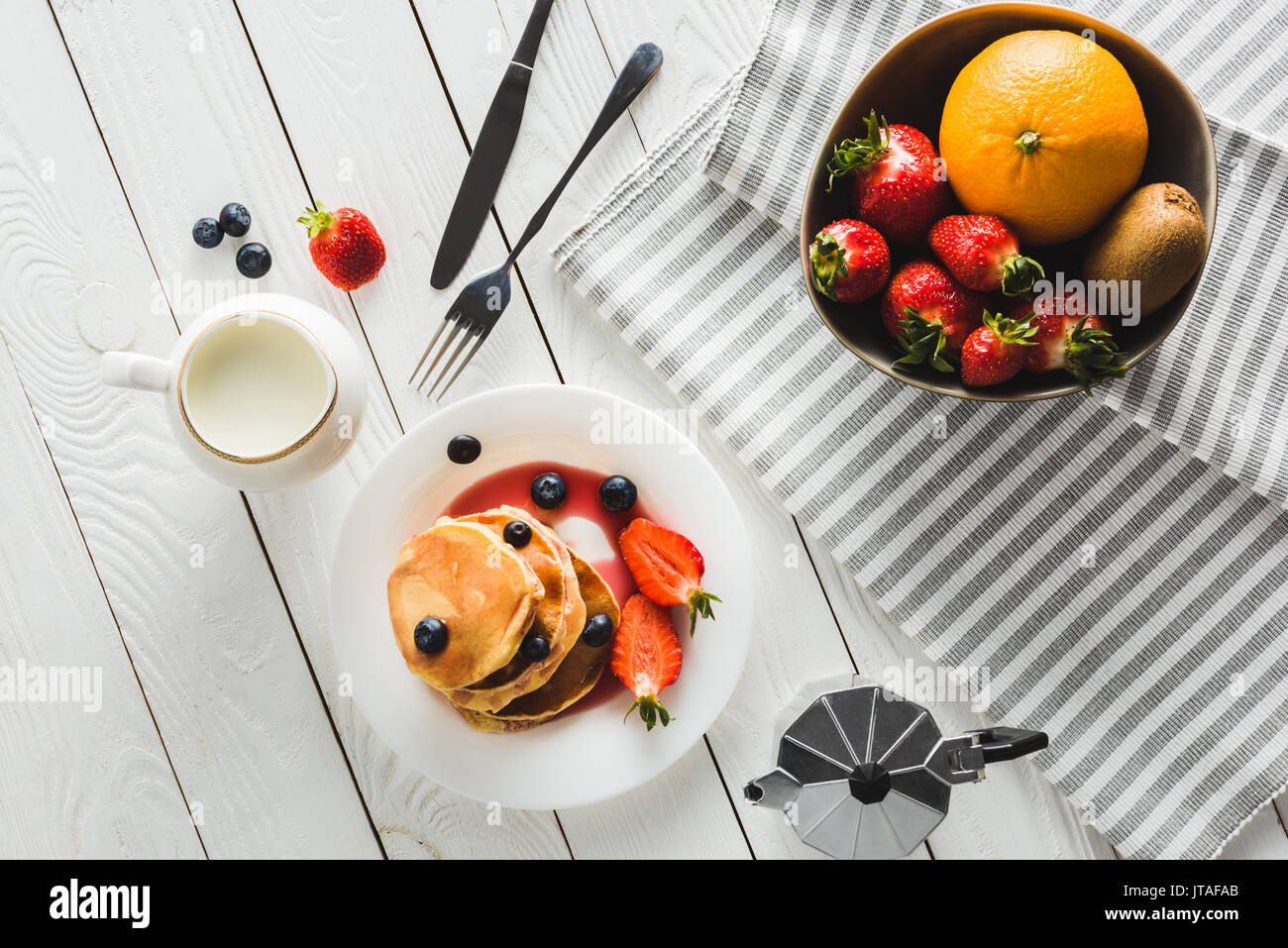 top view of homemade sweet pancakes and different fruits for healthy breakfast on wooden tabletop - Stock Image