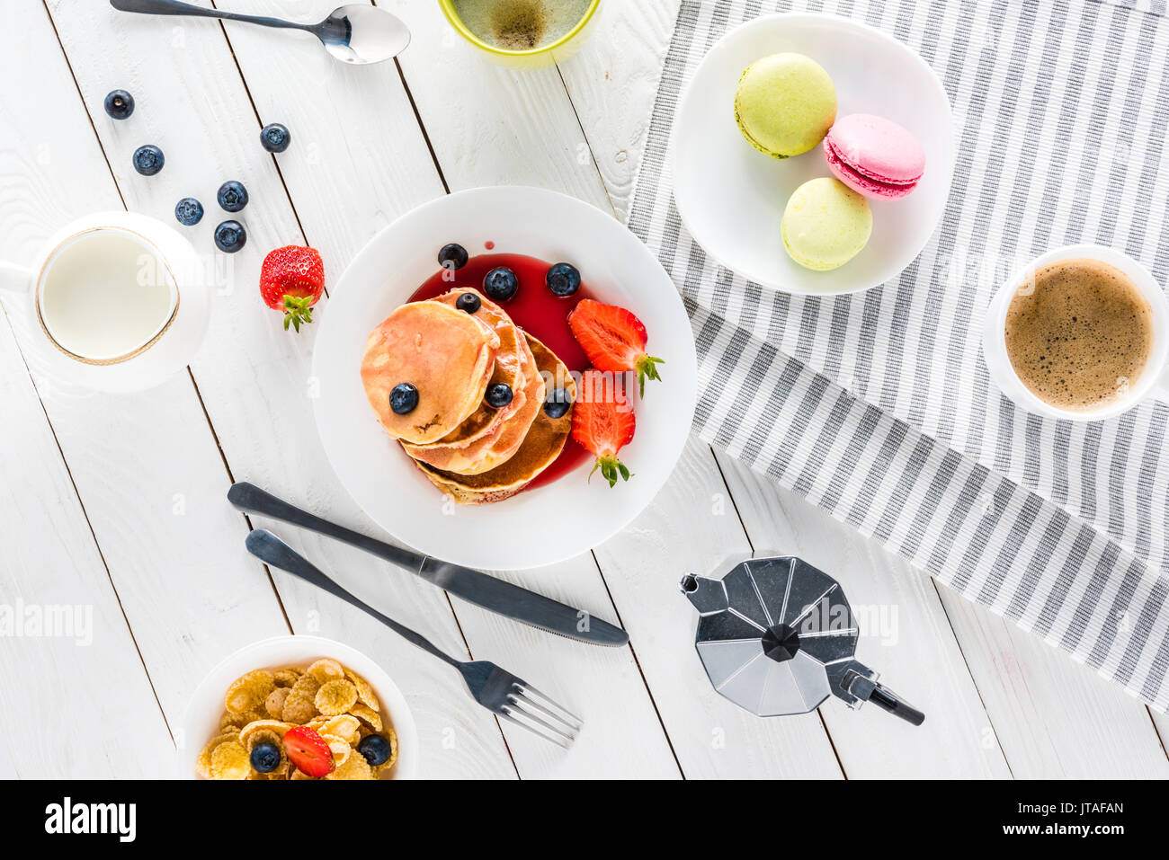 top view of pancakes with macarons and coffee with corn flakes on wooden tabletop - Stock Image