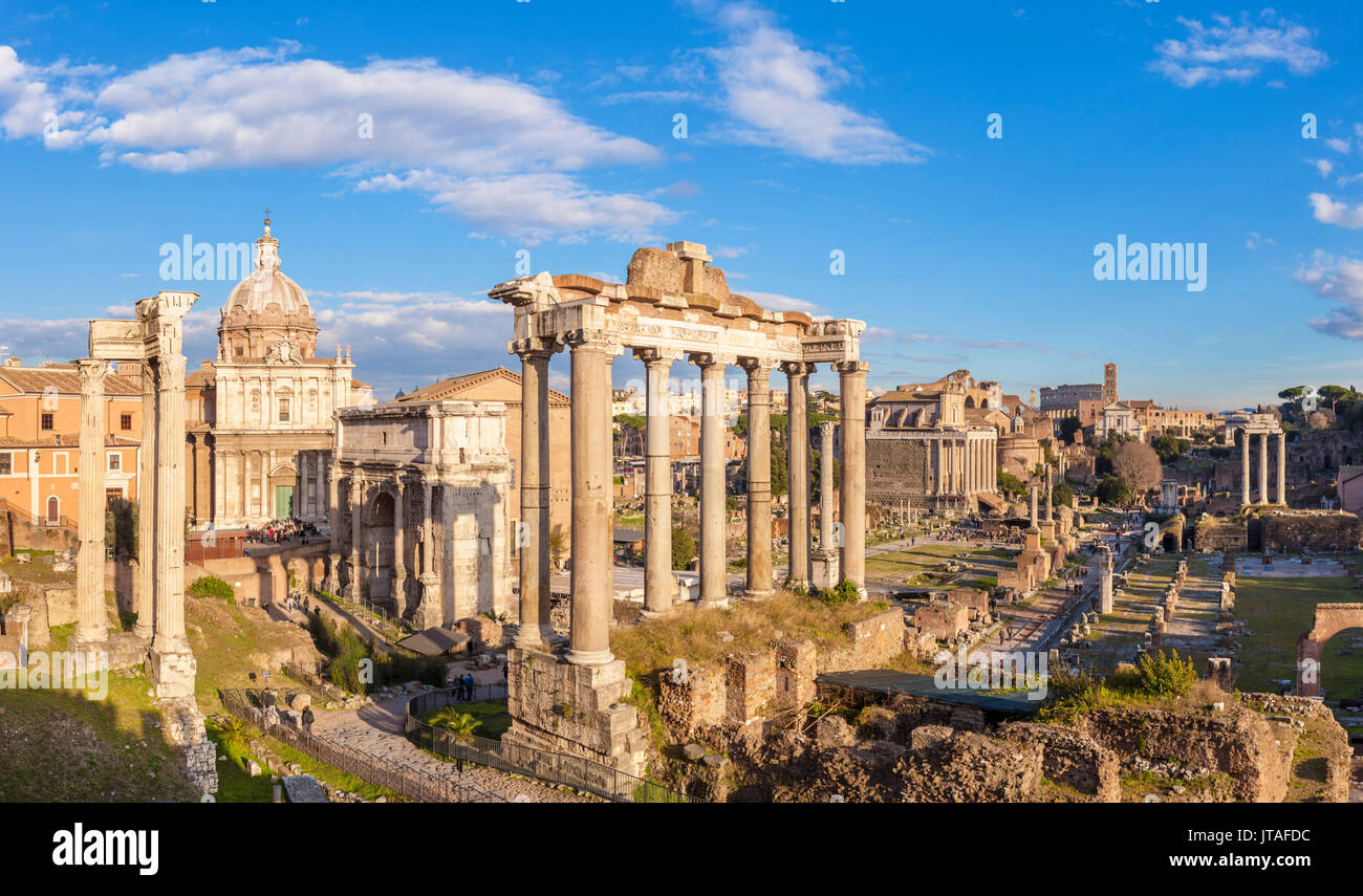 The columns of the Temple of Saturn and overview of the ruined Roman Forum, UNESCO, Rome, Lazio, Italy, Europe - Stock Image