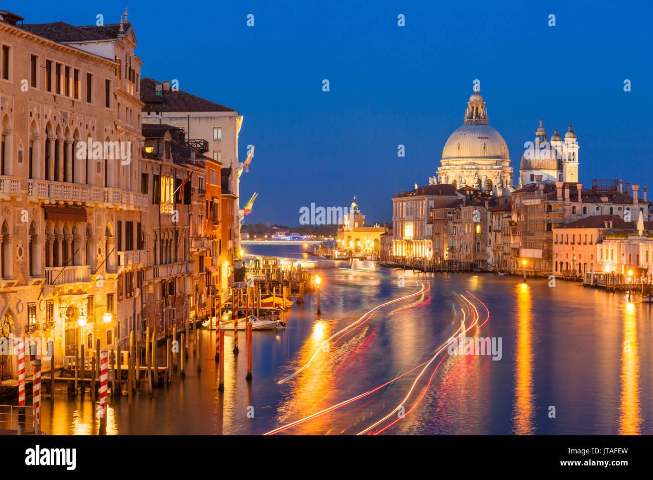 Grand Canal, and the church of Santa Maria della Salute, at night, with boat light trails, Venice, UNESCO, Veneto, Italy, Europe - Stock Image