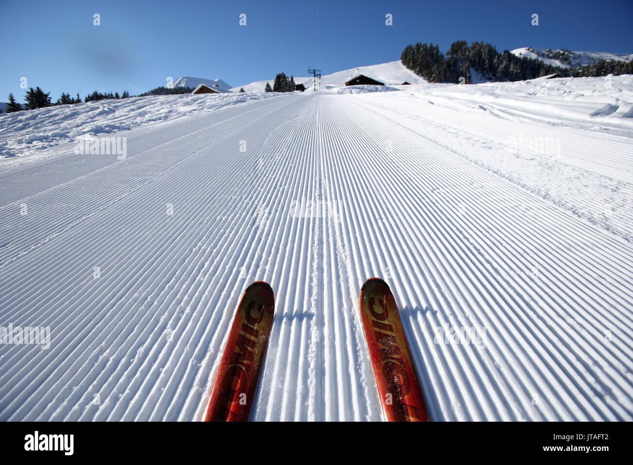 Red pair of ski in snow, groomed ski piste in the French Alps, Haute-Savoie, France, Europe - Stock Image
