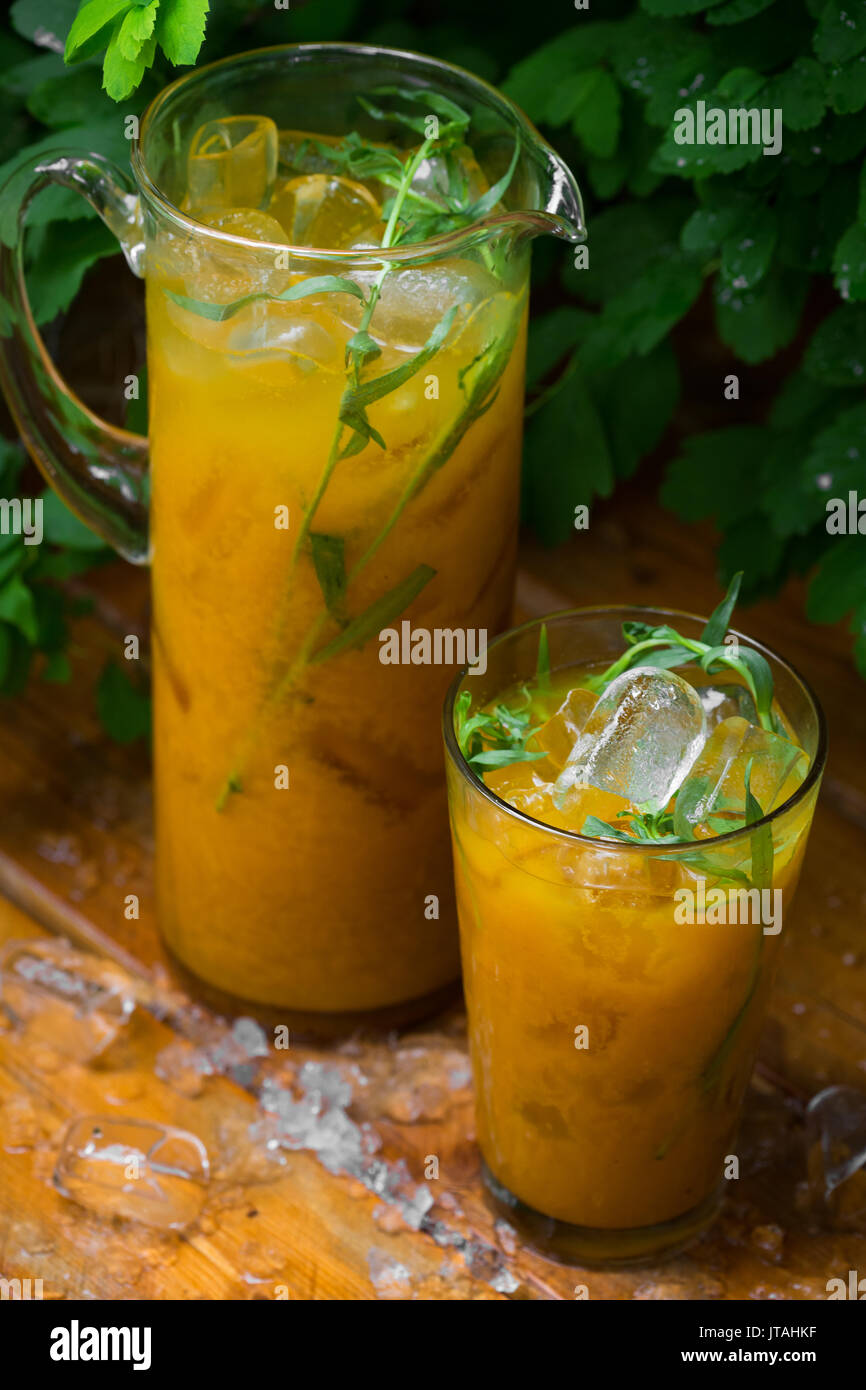 Citrus lemonade with herbs on a wooden background. Orange lemonade with tarragon. close up - Stock Image