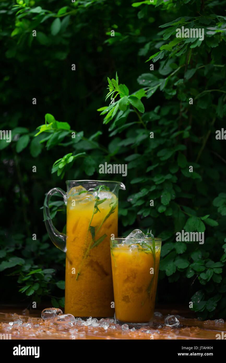 Citrus lemonade with herbs on a wooden background. Orange lemonade with tarragon - Stock Image