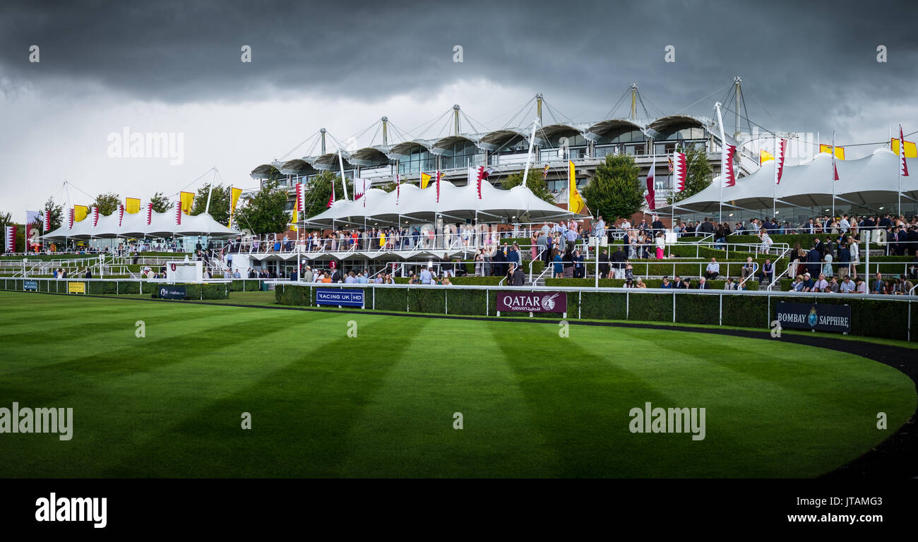 Storm clouds pass as people gather around the Paddock during Glorious Goodwood 2017 in West Sussex - Stock Image