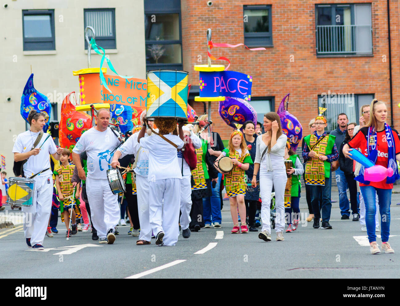 A group of males and females wearing colourful costumes celebrating Sma Shot Day on the streets of Paisley, Scotland on 1st July 2017 - Stock Image