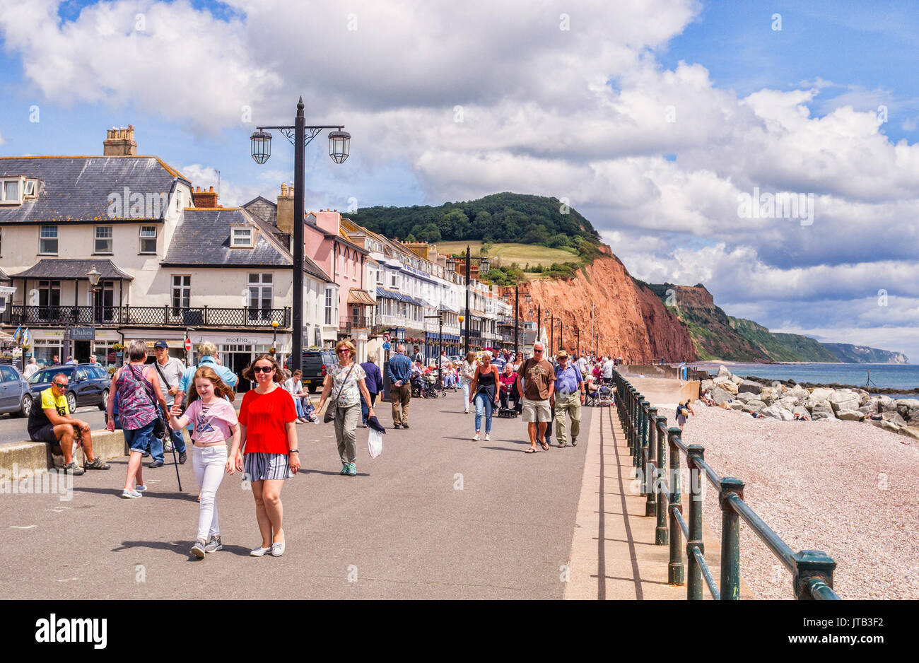 3 July 2017: Sidmouth, Dorset, England, UK - Visitors strolling on the promenade on a sunny summer day with blue sky and huge cumulus clouds. - Stock Image