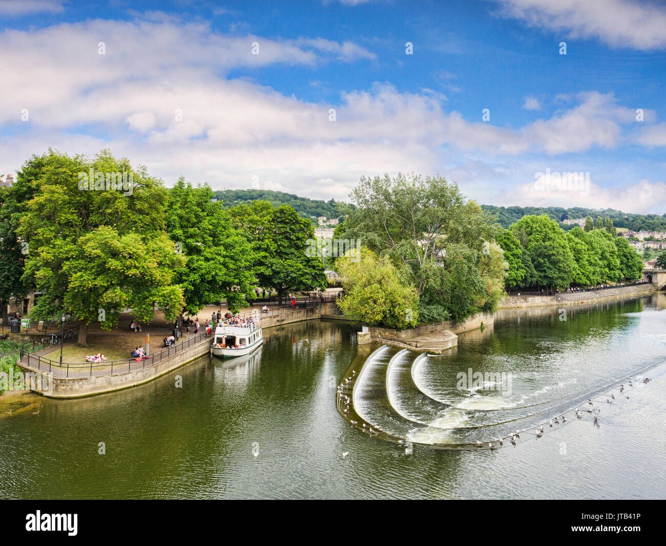 8 July 2017: Bath, Somerset, England, UK - Pulteney Weir, one of the attractions of the city, and a pleasure boat moored nearby. - Stock Image