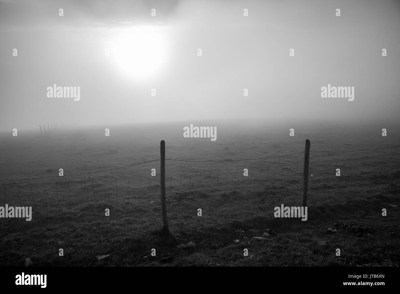 Morning sun filtered through fog on a mountain, with a fence silhouette - Stock Image