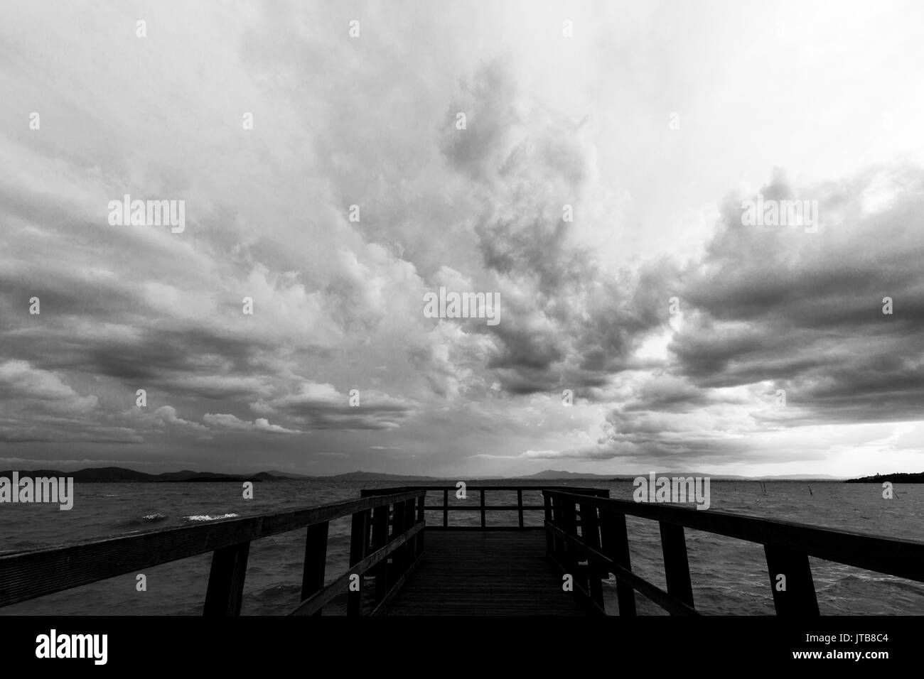 Geometric, first person view of a pier on a lake, beneath an overcast, moody sky - Stock Image