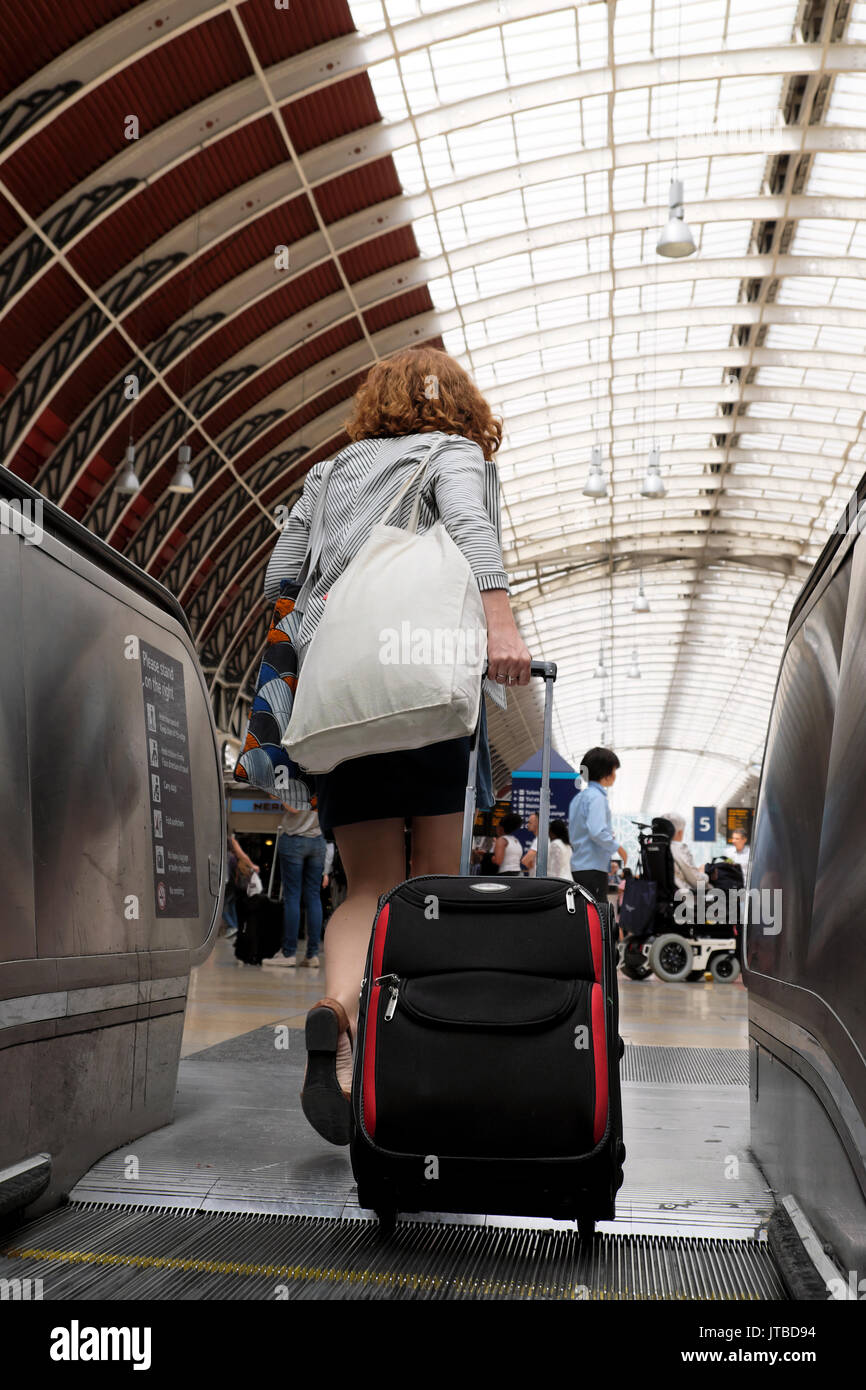 A view of the roof and a young woman with her luggage walking onto the concourse from an escalator at Paddington Stock Photo