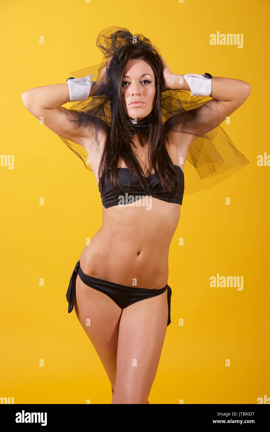 Beautiful brunette girl dancer in the studio wearing a black bikini and veil,  yellow background