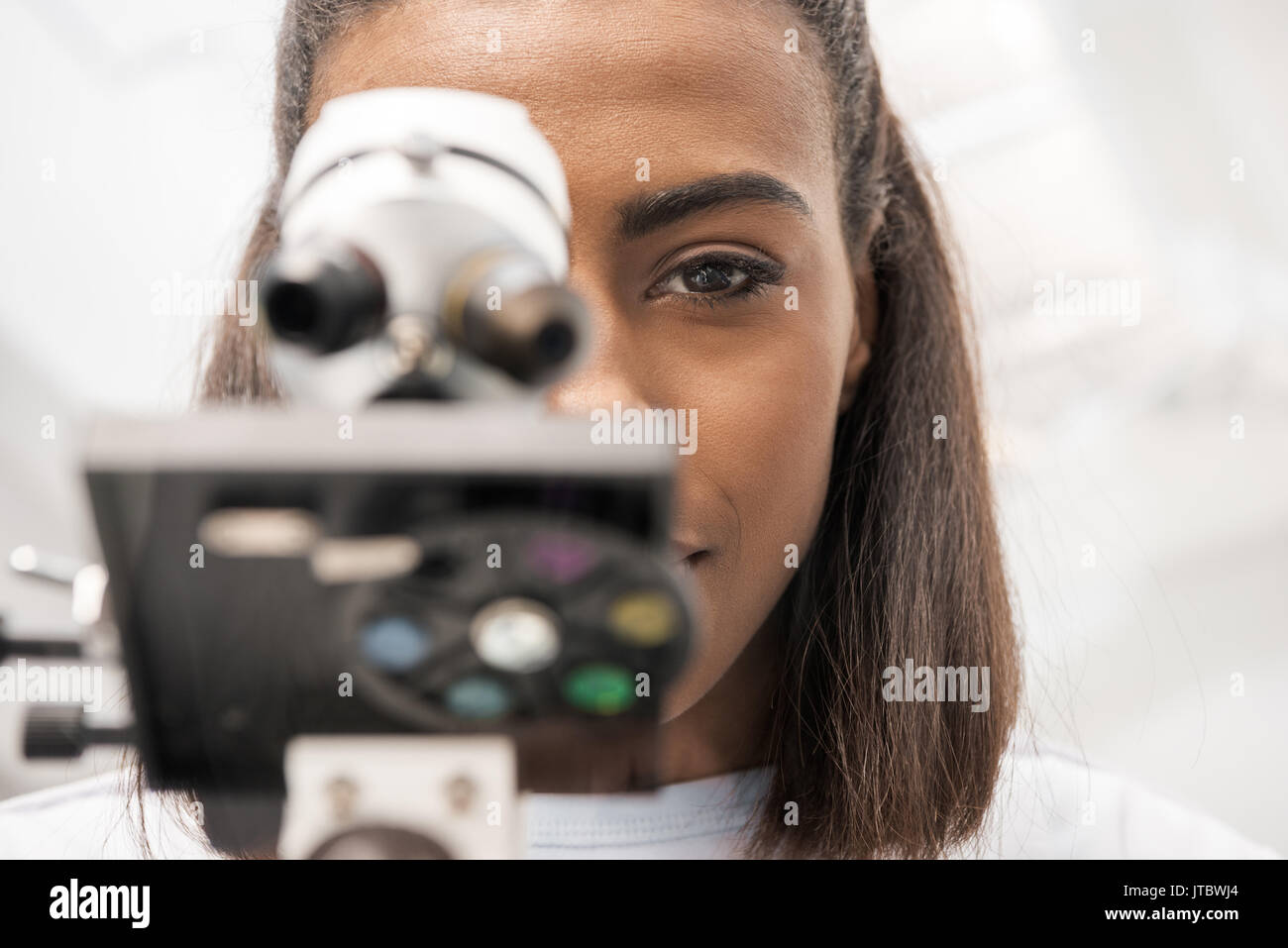 partial view of woman scientist looking through microscope on reagents in laboratory   - Stock Image