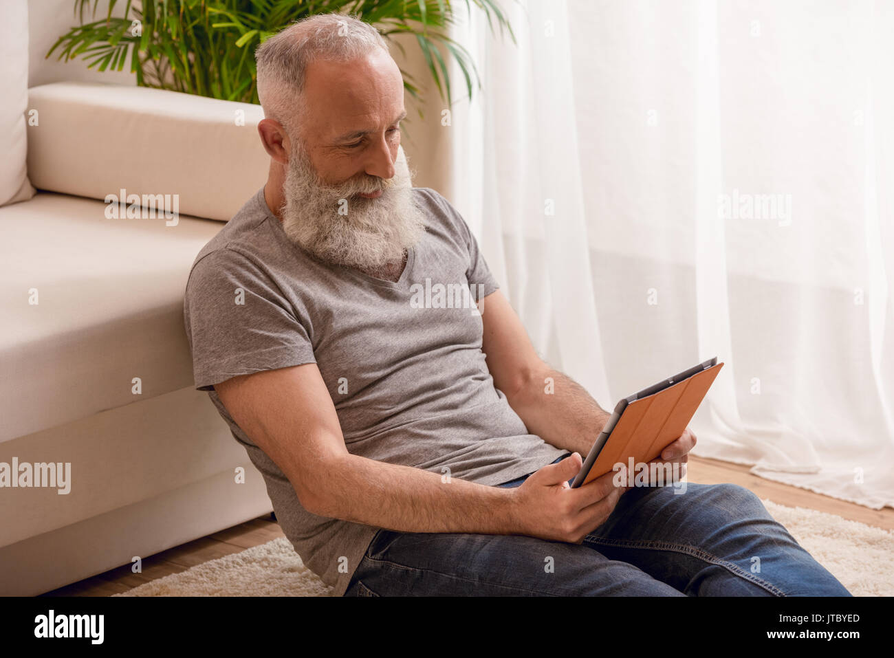 senior bearded man smiling and using digital tablet and sitting on floor at home - Stock Image