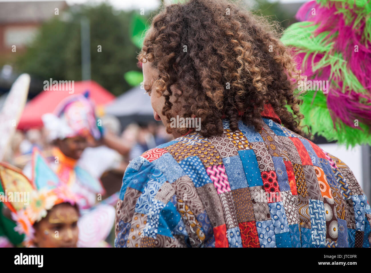 Show compere with dreadlock hair and bright coloured jacket entertains the crowd at the Stockton International Riverside Festival parade - Stock Image